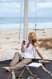海滩美丽的小船texting的妇女 库存照片