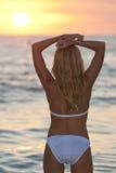 海滩美丽的比基尼泳装日落妇女 免版税库存图片