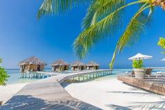 海滩美丽的蓝天 豪华热带海滩风景、豪华水别墅轻便折叠躺椅和懒人 免版税库存图片