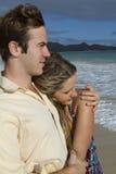 海滩美好的夫妇拥抱年轻人 免版税库存图片