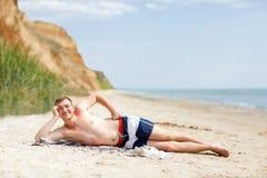 海滩背景的一个年轻人 说谎在沙子的一个微笑的人在蓝色海洋附近 背景概念框架沙子贝壳夏天 复制空间 免版税库存图片