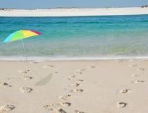 海滩脚印伞 免版税库存照片