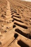 海滩脚印行业沙子拖拉机 库存照片
