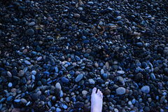 海滩英尺向白色扔石头 免版税库存图片