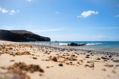 海滩蓝色黑暗的天空向火山扔石头 库存图片
