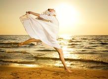 海滩跳的妇女 免版税库存照片