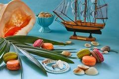 海滩辅助部件、新鲜的鲜美果子和macaron在蓝色背景 免版税库存图片