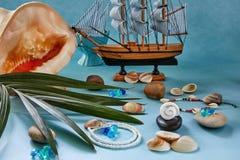 海滩辅助部件、贝壳和小船在蓝色背景 库存图片
