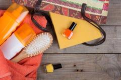 海滩辅助部件-发刷,橙色毛巾,太阳奶油,化妆水,海滩袋子,指甲油,在棕色木背景的一本书 库存图片