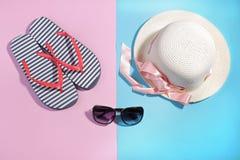 海滩辅助部件 啪嗒啪嗒的响声和一个夏天帽子有太阳镜的在明亮的桃红色和蓝色背景 顶视图 库存照片