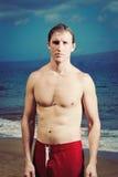 海滩适合的英俊的人年轻人 免版税图库摄影
