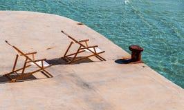 海滩面对太阳的轻便折叠躺椅在绿松石海和生锈的系船柱 免版税库存照片