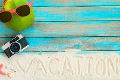 海滩顶视图铺沙用椰子、太阳镜、减速火箭的照相机、海星和壳在蓝色木背景 免版税图库摄影