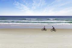 海滩骑自行车的人 库存图片