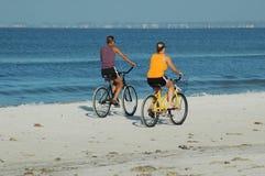 海滩骑自行车的人 免版税库存图片
