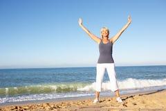 海滩高级舒展的妇女 免版税库存图片