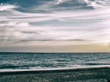 海滩,在海垂悬的云彩 免版税图库摄影