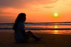 海滩12月享用女孩剪影坐的ot 免版税库存照片