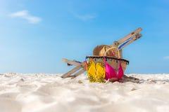 海滩formentera海岛妇女年轻人 比基尼泳装和啪嗒啪嗒的响声,帽子,鱼在沙滩的海滩睡椅附近担任主角并且请求反对蓝色海和天空背景, 免版税库存图片