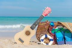 海滩formentera海岛妇女年轻人 比基尼泳装和啪嗒啪嗒的响声、帽子、尤克里里琴和袋子在海滩睡椅附近在沙滩反对蓝色海和天空背景, 库存图片