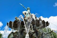 海王星喷泉在有水喷气机的柏林在蓝天背景的 免版税库存照片