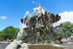 海王星喷泉在有水喷气机的柏林在蓝天背景的 库存图片