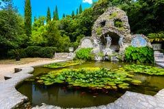 海王星的喷泉和百合在Trsteno,克罗地亚筑成池塘 免版税库存照片