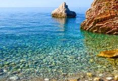 海的好的看法 由岸的风平浪静 清洗Pebble海滩和大石头 亚得里亚 黑山 免版税库存图片