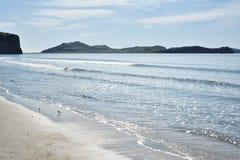 海的海岸有美丽的沙子的在一个晴天 库存图片