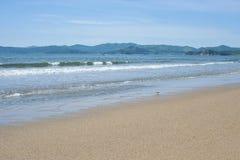 海的海岸有美丽的沙子的在一个晴天 免版税库存图片