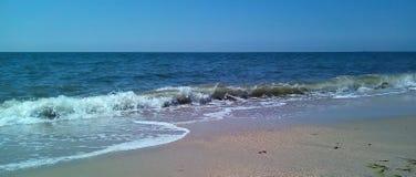 海的看法从岸的在一好日子 有轻的波纹的风平浪静水和小波浪的表面上 免版税库存照片
