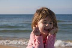 海的笑的小女孩背景 免版税库存图片