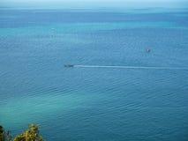 海的表面上的汽船在海岛附近的 库存图片