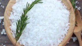 海盐和迷迭香在一个木碗有匙子的在桌上 股票录像