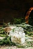 海盐用在一个玻璃瓶子的干迷迭香,葡萄酒木后面 库存图片