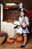 海盗服装的滑稽的女孩在有风景的演播室为万圣夜 免版税图库摄影