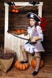 海盗服装的滑稽的女孩在有风景的演播室为万圣夜 免版税库存照片