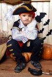 海盗服装的滑稽的男孩在有风景的演播室为万圣夜 免版税库存图片