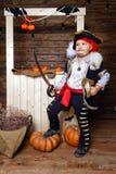 海盗服装的滑稽的男孩在有风景的演播室为万圣夜 库存图片