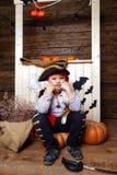 海盗服装的滑稽的男孩在有风景的演播室为万圣夜 免版税库存照片