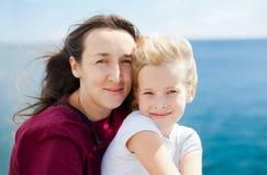 海背景的母亲和女儿 库存图片