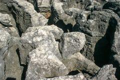 海腐蚀的巨大的岩石在午间太阳之前点燃了 免版税图库摄影