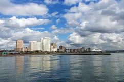 海蓝色多云天空和金黄英里城市地平线 库存照片