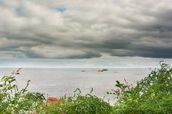 海表面天空阴云密布草和石头 库存照片