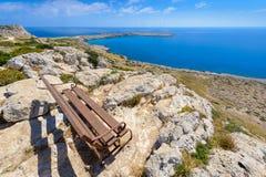 海角格雷科海岸线长凳视图,塞浦路斯 免版税库存照片