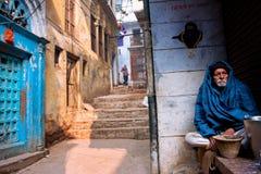 海角的年长人单独坐古老印度城市的街道 免版税库存图片