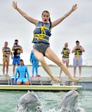 海豚扔女孩在水外面 免版税库存照片