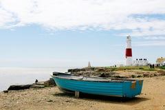 海边、小船和灯塔在波特兰,多西特,英国 免版税库存照片