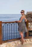 海边大阳台的女孩 免版税库存照片