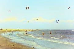 海边沐浴者&桨手包括风筝 免版税库存图片